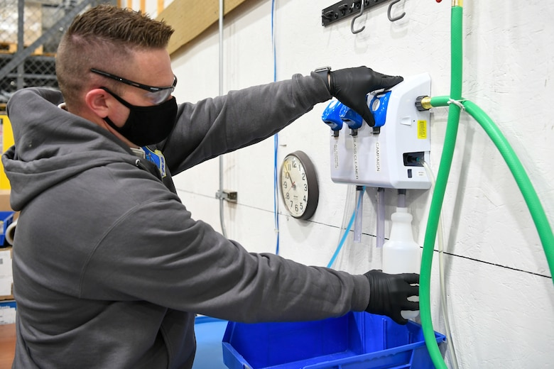 Jeremy Stewart, 309th Maintenance Support Group hazmat shop supervisor, fills up spray bottles with cleaning disinfectant.