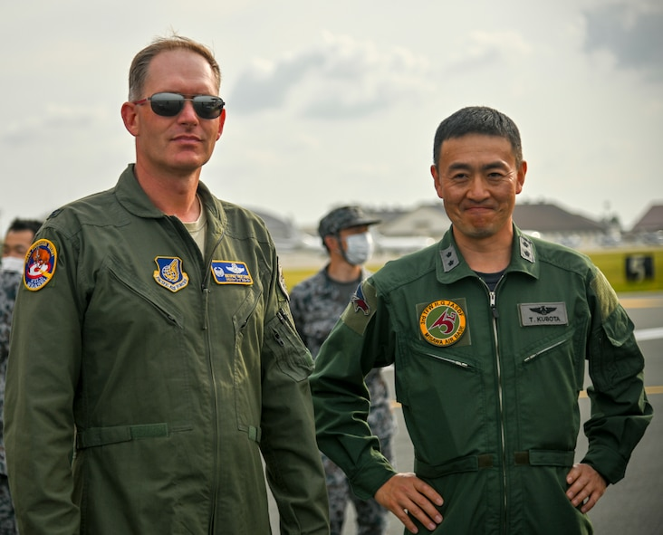 """U.S. Air Force Col Kristopher Struve, left, 35th Fighter Wing commander, and Japan Air Self-Defense Force Maj. Gen. Takahiro Kubota, 3rd Air Wing and JASDF Misawa Air Base commander, watch as aircraft taxi into position for an """"Elephant Walk"""" at Misawa Air Base, June 22, 2020. Twelve U.S. Air Force F-16CM Fighting Falcons, 12 Koku-Jieitai F-35A Lightning II Joint Strike Fighters, two U.S. Navy EA-18G Growlers, a USN C-12 Huron, two USAF MC-130J Commando II aircraft, and a USN P-8 Poseidon participated in the Elephant Walk, which showcased Misawa Air Base's collective readiness and ability to generate combat airpower at a moment's notice to ensure regional stability throughout the Indo-Pacific. This is Misawa Air Base's first time hosting a bilateral and joint Elephant Walk. (U.S. Air Force photo by Tech. Sgt. Timothy Moore)"""