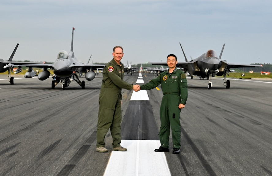 """U.S. Air Force Col Kristopher Struve, left, 35th Fighter Wing commander, and Japan Air Self-Defense Force Maj. Gen. Takahiro Kubota, 3rd Air Wing and JASDF Misawa Air Base commander, shake hands in front of aircraft participating in an """"Elephant Walk"""" at Misawa Air Base, June 22, 2020. Twelve U.S. Air Force F-16CM Fighting Falcons, 12 Koku-Jieitai F-35A Lightning II Joint Strike Fighters, two U.S. Navy EA-18G Growlers, a USN C-12 Huron, two USAF MC-130J Commando II aircraft, and a USN P-8 Poseidon participated in the Elephant Walk, which showcased Misawa Air Base's collective readiness and ability to generate combat airpower at a moment's notice to ensure regional stability throughout the Indo-Pacific. This is Misawa Air Base's first time hosting a bilateral and joint Elephant Walk. (U.S. Air Force photo by Tech. Sgt. Timothy Moore)"""