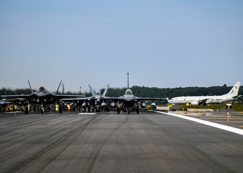 """Twelve U.S. Air Force F-16CM Fighting Falcons, 12 Koku-Jieitai F-35A Lightning II Joint Strike Fighters, two U.S. Navy EA-18G Growlers, a USN C-12 Huron, two USAF MC-130J Commando II aircraft, and a USN P-8 Poseidon participate in an """"Elephant Walk"""" at Misawa Air Base, June 22, 2020. The Elephant Walk showcased Misawa Air Base's collective readiness and ability to generate combat airpower at a moment's notice to ensure regional stability throughout the Indo-Pacific. This is Misawa Air Base's first time hosting a bilateral and joint Elephant Walk."""