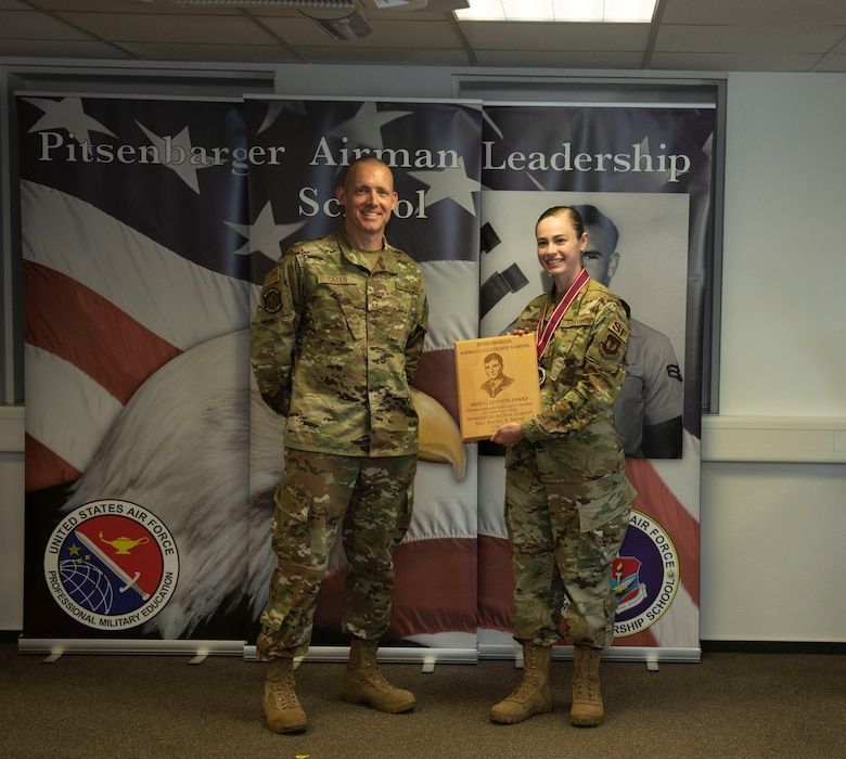 U.S. Air Force Chief Master Sgt. William Cates, 726th Air Mobility Squadron superintendent, left, presents the John L. Levitow award to Staff Sgt. Rachel Brown, 52nd Security Forces Squadron member, during the Pitsenbarger Airman Leadership School class 20-E graduation at Spangdahlem Air Base, Germany, June 19, 2020. The award is given to the ALS graduate who demonstrates the most outstanding professional leadership and academic performance. (U.S. Air Force photo by Senior Airman Melody W. Howley)