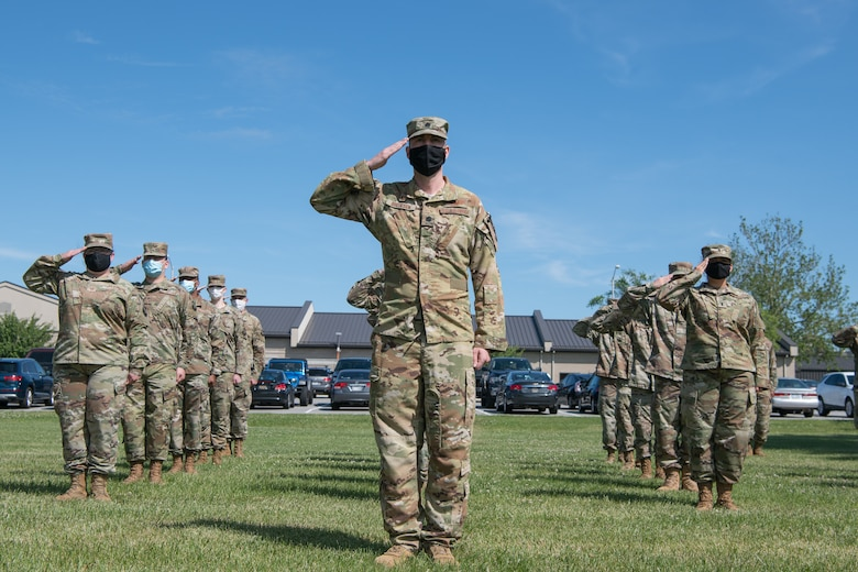 Airmen of the 436th Operations Support Squadron salute during a retreat ceremony June 18, 2020, at Dover Air Force Base, Delaware. Members of the formation were spaced at least six feet apart and wore masks to help mitigate the potential spread of COVID-19. (U.S. Air Force photo by Mauricio Campino)