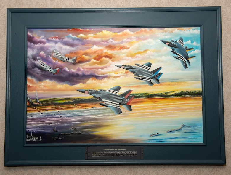 A painting depicting the 48th Fighter Wing heritage F-15s was presented to the wing and Col. William Marshall, 48th FW commander, at Royal Air Force Lakenheath, England, June 19, 2020. The painting is a tribute to 48th FW history and it's involvement in D-Day at Normandy, France during World War II. (U.S. Air Force photo by Airman 1st Class Jessi Monte)
