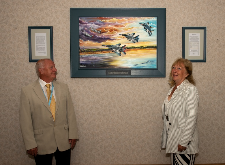 Colin Mason, 48th Mission Support Group Honorary commander, and his wife Elizabeth, stand next to the artwork they created for the 48th Fighter Wing at Royal Air Force Lakenheath, England, June 19, 2020. The painting is a tribute to 48th FW history and it's involvement in D-Day at Normandy, France during World War II. (U.S. Air Force photo by Airman 1st Class Jessi Monte)