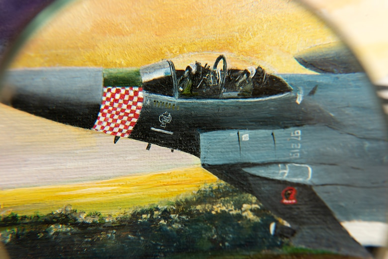 Fine details can be seen through a magnifying glass on a painting presented on behalf of Colin Mason, 48th Mission Support Group Honorary commander, and his wife Elizabeth, to the 48th Fighter Wing at Royal Air Force Lakenheath, England, June 19, 2020. The painting is a tribute to 48th FW history and it's involvement in D-Day at Normandy, France during World War II. (U.S. Air Force photo by Airman 1st Class Jessi Monte)
