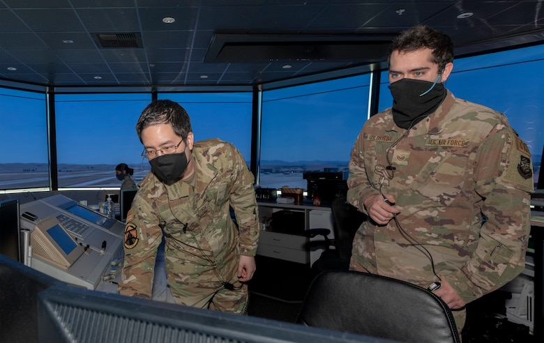 U.S. Air Force Staff Sgt. Drew Tsubota, left, 60th Operation Support Squadron air traffic control journeyman and Staff Sgt. Shane Goldstedt, right, 921st Contingency Response Squadron ATC journeyman, monitor aircraft in the control tower May 5, 2020, Travis Air Force Base, California. The coronavirus pandemic has had a minimal impact on the Travis Control Tower team's 24/7mission. Air traffic controllers promote the orderly, safe and expeditious flow of air traffic under both visual and instrument controls by issuing advisories, instructions and clearances. (U.S. Air Force photo by Heide Couch)
