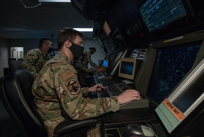 U.S. Air Force air traffic controllers assigned to the 60th Operations Support Squadron Radar Approach Control, monitor the airspace May 5, 2020, at Travis Air Force Base, California. The coronavirus pandemic has affected RAPCON daily operations due to the significant decrease in civilian and military air traffic. To help mitigate the spread of the coronavirus, the RAPCON has reduced the size of the crews on duty in addition to requiring cloth face coverings, and the frequent sanitization of the touch screen equipment. (U.S. Air Force photo by Heide Couch)