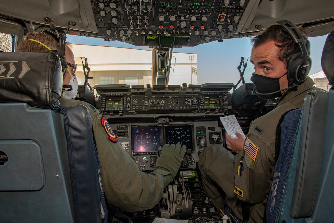 U.S. Air Force Lt. Col Michael Pettibone, left, and 1st Lt. John Massey, 21st Airlift Squadron pilots, conduct preflight operations in the flight deck of a C-17 Globemaster III May 6, 2020, at Travis Air Force Base, California. Aircrews have adapted to meet Department of Defense requirements to minimize the spread of the coronavirus and to prioritize health and safety by using personal protective equipment and sanitizing flight controls. (U.S. Air Force photo by Heide Couch)