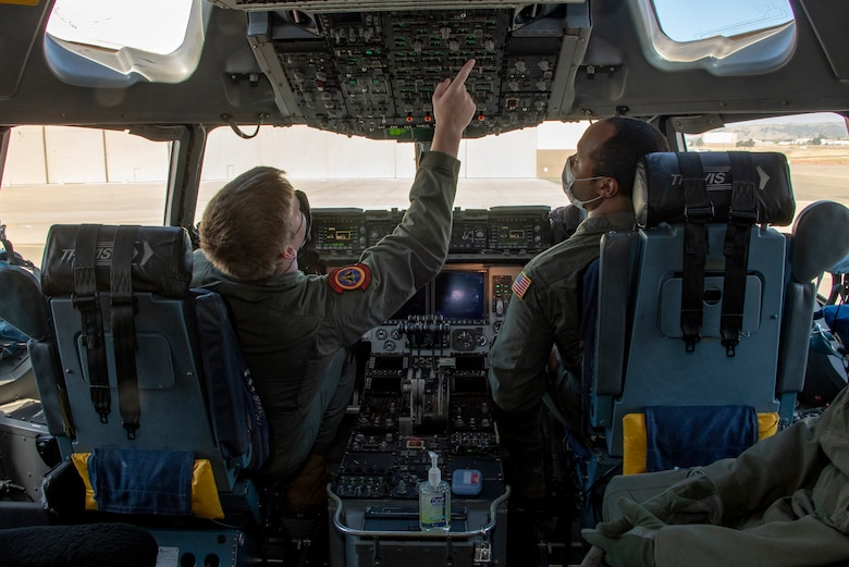 U.S. Air Force Airman 1st Class Eric Vanderford, left, 21st Airlift Squadron loadmaster, and Master Sgt. Jesse Williams, 21st AS instructor loadmaster, conduct preflight operations in the flight deck of a C-17 Globemaster III May 6, 2020, at Travis Air Force Base, California. Aircrews have adapted to meet Department of Defense requirements to minimize the spread of the coronavirus and to prioritize health and safety by using personal protective equipment and sanitizing flight controls. (U.S. Air Force photo by Heide Couch)
