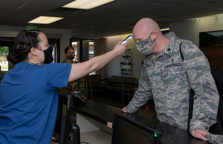 U.S. Air Force Airman 1st Class Kiarra Vendrell, left, 60th Dental Squadron dental technician, takes the temperature of Lt. Col. Thomas Weber, right, 60th DS dentist, June 6, 2020, at Travis Air Force Base, California. Dental clinic staff and patients are screened for COVID-19 symptoms prior to reporting to duty or appointments. (U.S. Air Force photo by Heide Couch