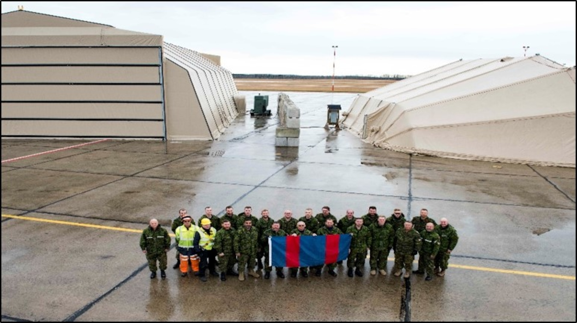 Members of 4 Wing, Cold Lake, Alberta, stand in front of a newly assembled Expeditionary Forces Aircraft Shelter System (EFASS) and a Mobile Support Shelter – Aircraft (MSS – A), in the fall of 2019.