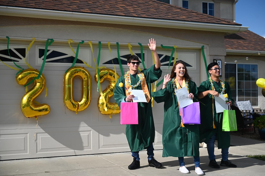 """Sean Santos, left, Makayla Kearny, center, and Jackson Reams, right, wave during the """"honk at a grad"""" parade, June 12, 2020, at Travis Air Force Base, California. The base's Air Force Sergeants Association Chapter 1320, Airman and Family Readiness Center, and chaplain corps celebrated high school seniors unable to experience a graduation ceremony due to the COVID-19 pandemic. (U.S. Air Force photo by Airman 1st Class Karla Parra)"""