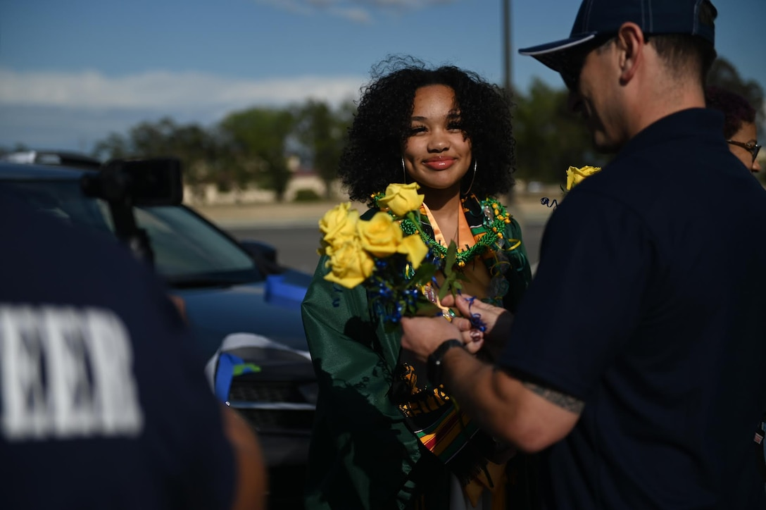 "U.S Air Force Senior Master Sgt. Rey Rios, Air Force Sergeants Association Chapter 1320 senior advisor, gives a rose to Cheyenne Robinson, a Vanden High School graduate, June 12, 2020, at Travis Air Force Base, California. The base's local AFSA Chapter 1320, Airman and Family Readiness Center, and chaplain corps collaborated for the ""honk at a grad"" parade to celebrate high school graduates unable to experience a graduation ceremony during the COVID-19 pandemic. (U.S. Air Force photo by Airman 1st Class Karla Parra)"
