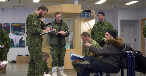 Reconnaissance team members from 2 Air Expeditionary Wing interview the Rankin Inlet Airport manager during their survey visit to Rankin Inlet, Nunavut, Jan. 28, 2020.