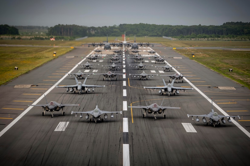 U.S. Navy, Air Force and Japanese air force aircraft sit on a runway.