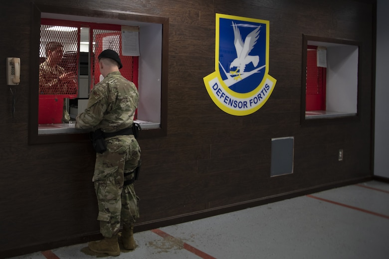 A Security Forces defender stands at the 316th Security Support Squadron armory window to receive the weapons and equipment for his shift on Joint Base Andrews, Md., June 17, 2020. The armory also houses weapons for general officers and personnel living on base.