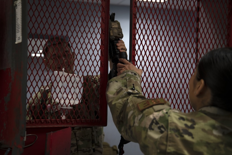 Senior Airman Cindy Argueta, 316th Security Support Squadron armorer, hands off an M4 carbine to Airman 1st Class Julian Almazan, 316th Security Forces Squadron defender, before his shift on Joint Base Andrews, Md., June 17, 2020. Defenders are issued a minimum of one lethal force weapon, one less than lethal force weapon, and a radio before each shift.