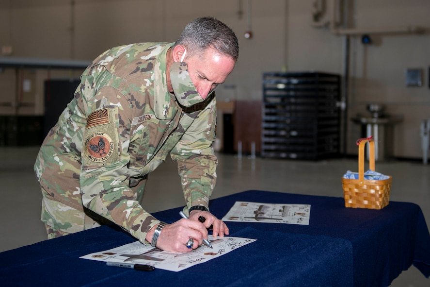 Air Force Chief of Staff Gen. David L. Goldfein signs a lithograph after visiting Creech Air Force Base, Nevada.