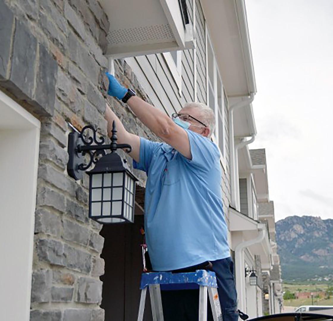 Mark Chamberlain, residential maintenance technician, Balfour Beatty Communities, repairs a gutter June 9 at a home in the Cherokee Village neighborhood at Fort Carson, Colorado.