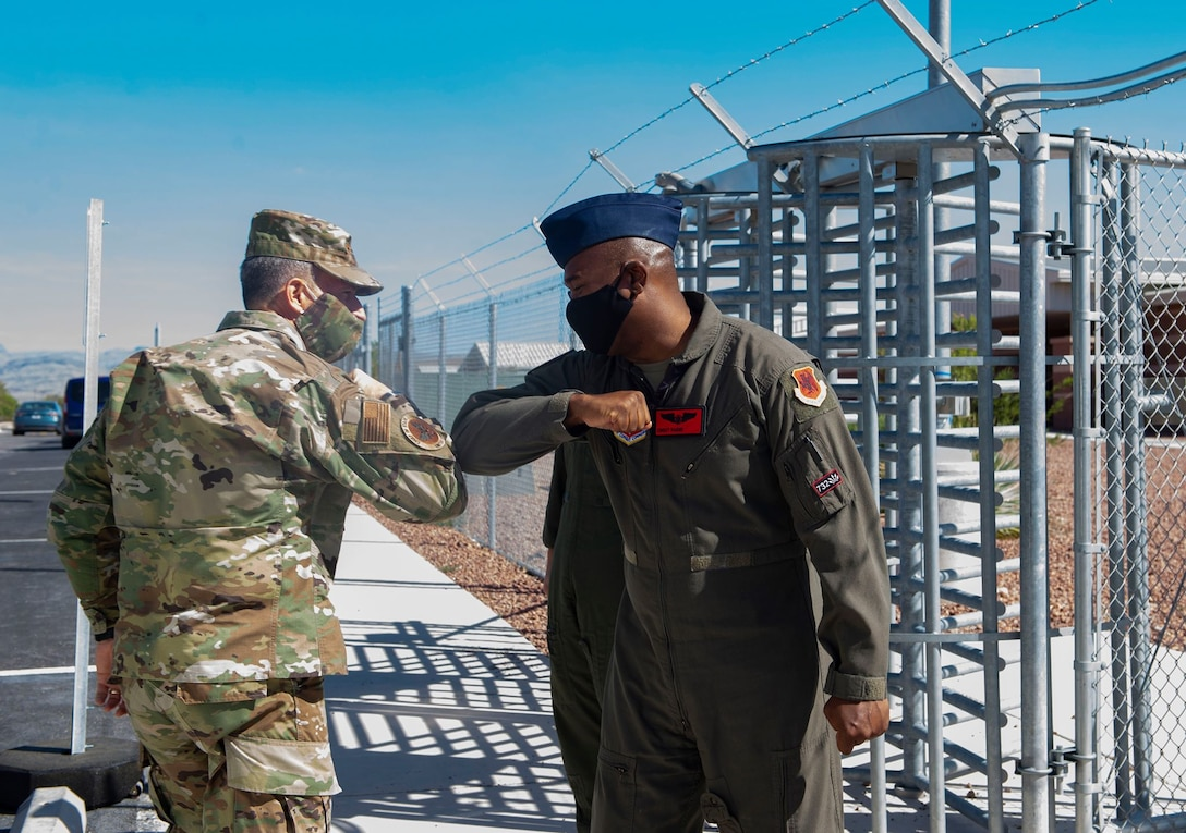 Air Force Chief of Staff Gen. David L. Goldfein greets Chief Master Sgt. Roderick with an elbow touch due to COVID-19 procedures outside of the 17th Attack Squadron.