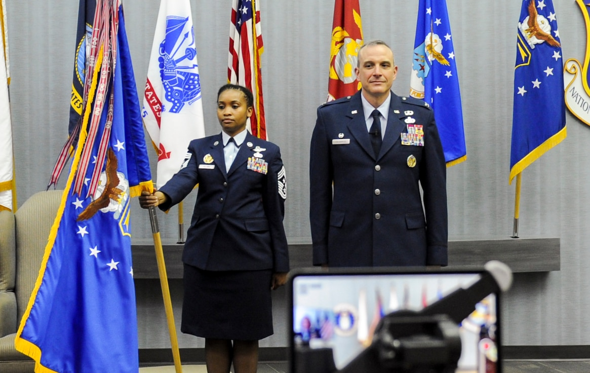 Chief Master Sgt. Kimberly Pollard, National Air and Space Intelligence Center Command Chief, stands with the NASIC flag during a ceremony honoring Col. Maurizio Calabrese as he assumed command of the Center June 9, 2020.