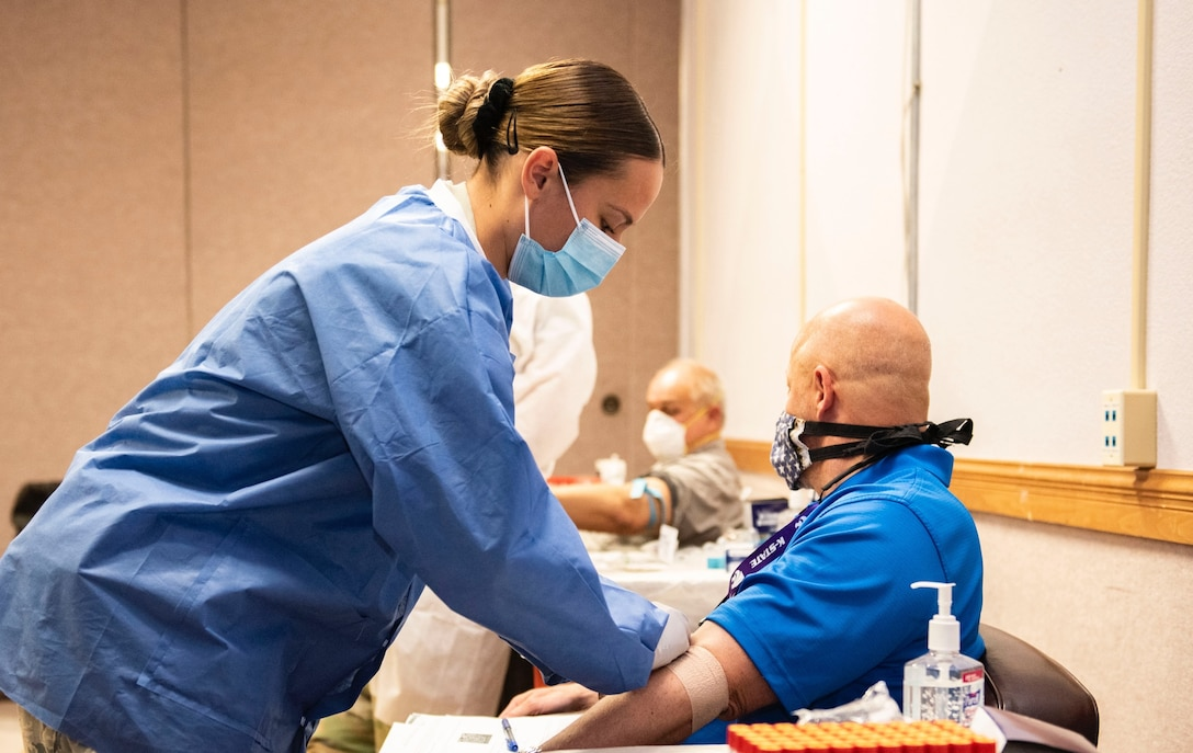 Lab Tech wraps a bandage on patient.