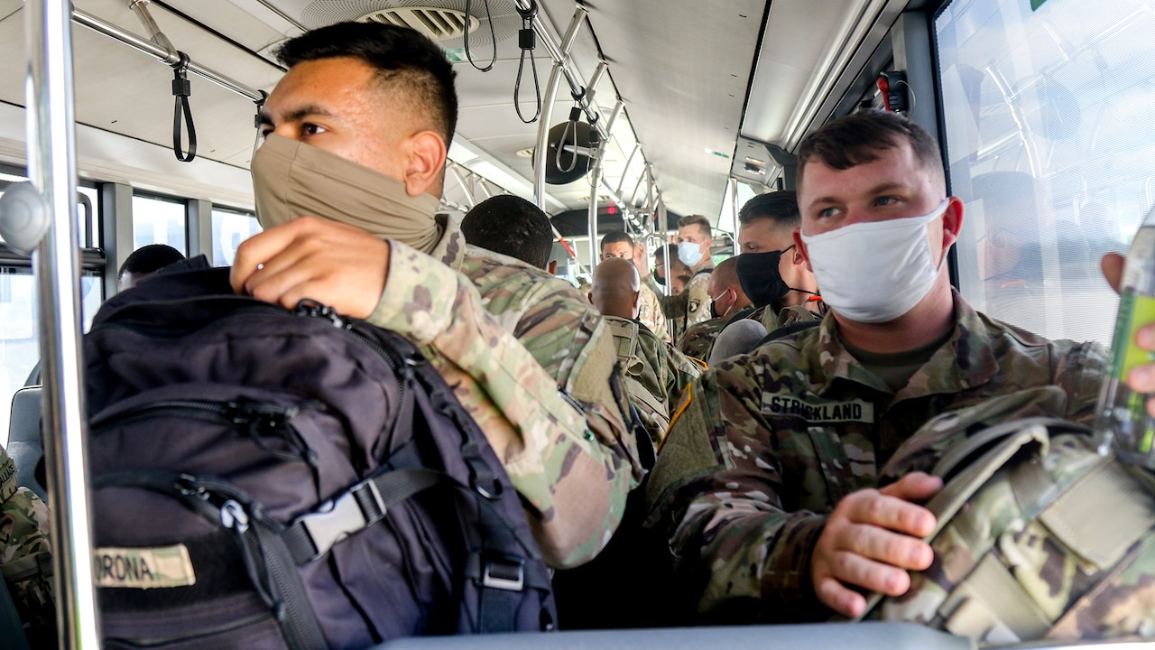 Two soldiers wearing face masks and holding backpacks on their laps sit in a bus.