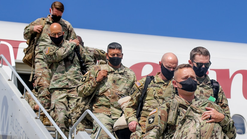 Soldiers wearing face masks disembark from an airliner.