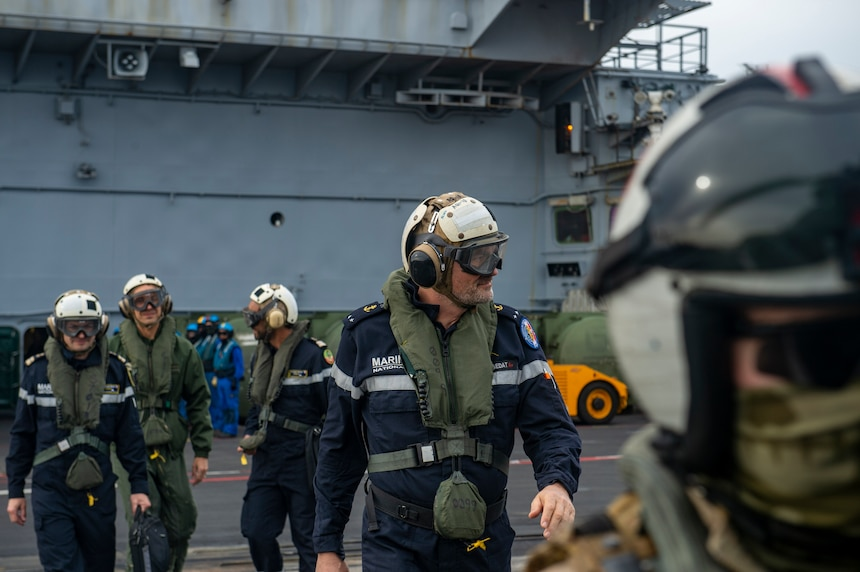 Rear-Admiral Marc Aussedat, commander, French Marine Nationale, walks across the flight deck of the French aircraft carrier FS Charles de Gaulle (R91) during an integrated operations exercise with aircraft carrier USS Dwight D. Eisenhower (CVN 69). Ike is conducting operations in the Mediterranean Sea as part of the USS Dwight D. Eisenhower Carrier Strike Group.
