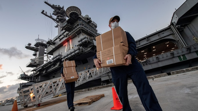 Sailors wearing masks receive boxes of Meals, Ready to Eat, for those quarantined on the USS Theodore Roosevelt.
