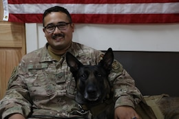 U.S. Air Force Staff Sgt. Juan Reyes sits with his Military Working Dog partner Cvoky in Kuwait on June 16, 2020. The team visited Kuwait to seek treatment after Cvoky suffered a heat injury. ( U.S. Army National Guard photo by Trevor Cullen)