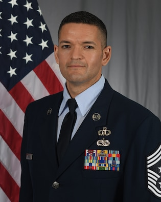 shoulder length photo 89th Airlift Wing commander with US flag in background