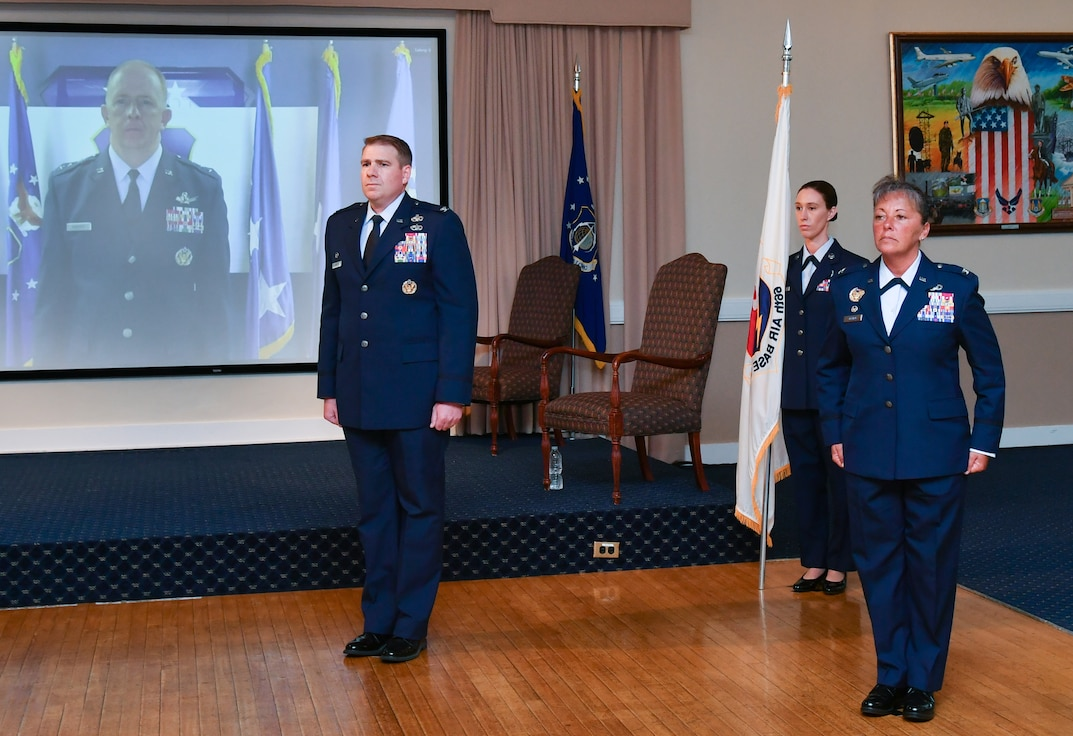 Col. Katrina Stephens stands at attention next to Col. Chad Ellsworth during the 66th Air Base Group change of command ceremony at Hanscom Air Force Base, Mass., while Lt. Gen. Robert McMurry, Air Force Life Cycle Management Center commander, looks on via teleconference. Stephens is taking command of the group after serving as the vice commander of the 78th Air Base Wing at Robins AFB, Ga., and is returning to Hanscom, where she served early in her Air Force career. (U.S. Air Force photo by Linda LaBonte Britt)