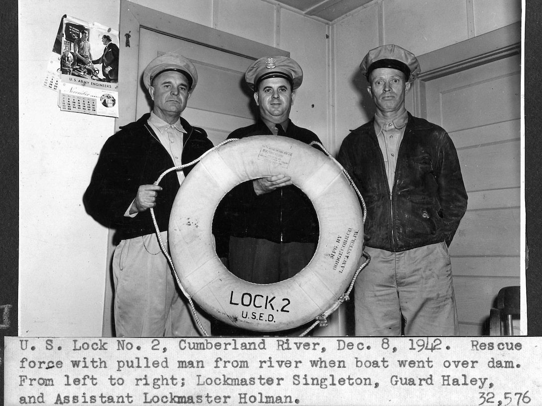 (Left to Right) Lockmaster Singleton, Guard Haley and Assistant Lockmaster Holman of the U.S. Army Corps of Engineers Nashville District pose after rescuing a man when his boat went over Dam 2 on the Cumberland River in Nashville, Tennessee, Dec. 8, 1942. (USACE Photo)