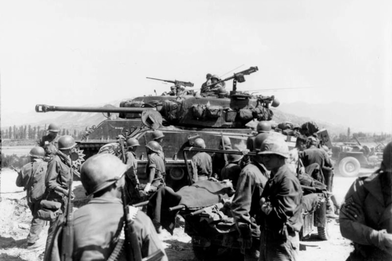 Combat casualties are carried past a tank.