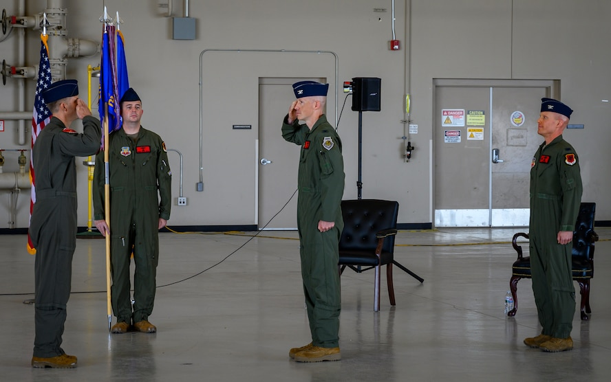 U.S. Air Force Col. John Powers, center, 432nd Operations Group commander, assumes command from presiding official Col. Stephen Jones, left, 432nd Wing/432nd Air Expeditionary Wing commander, during the 432nd OG change of command ceremony at Creech Air Force Base.