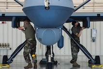 Airmen wearing facemasks compete to arm an MQ-9 Reaper during a quarterly load crew competition.