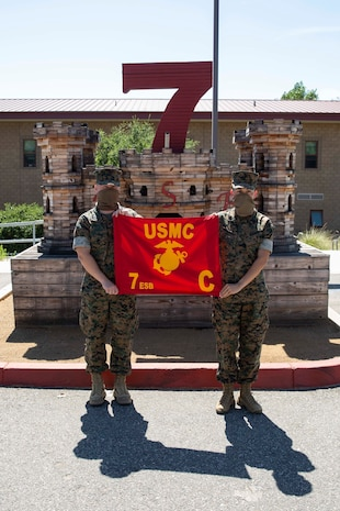 """Capt. Micah Tate and GySgt. Valerie Wofford hold the Company """"C"""" guidon in front of the 7th Engineer Support Battalion (7th ESB) headquarters building on Camp Pendleton, California, June 23, 2020. Company """"C,"""" 7th ESB, 1st MLG was activated June 22, on Camp Pendleton, California, to continue to train to conduct multiple functions of general engineering along with nonstandard gap crossing engineering reconnaissance mission capabilities to enhance the mobility of I Marine Expeditionary Force. (U.S. Marine Corps Photo by Sgt. Maximiliano Rosas)"""