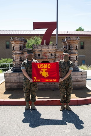 "Capt. Micah Tate and GySgt. Valerie Wofford hold the Bridge Company guidon in front of the 7th Engineer Support Battalion (7th ESB), headquarters building on Camp Pendleton, California, June 23, 2020. Bridge Company, 7th ESB, 1st Marine Logistics Group (1st MLG) was deactivated on June 22, on Camp Pendleton, California. Company ""C,"" 7th ESB, 1st MLG was activated the same day to continue to train to conduct multiple functions of general engineering along with nonstandard gap crossing engineering reconnaissance mission capabilities to enhance the mobility of I Marine Expeditionary Force. (U.S. Marine Corps Photo by Sgt. Maximiliano Rosas)"