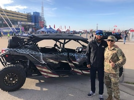 Bubba Wallace, the driver of the Air Force-sponsored Richard Petty Motorsport's No. 43 car, poses with Tech. Sgt. Alvin Llamas, of the 349th Recruiting Squadron, in front of the squadron's Bounty Hunter prior to the Hollywood Casino 400 race October, 20, 2019 in Kansas City, Kansas.