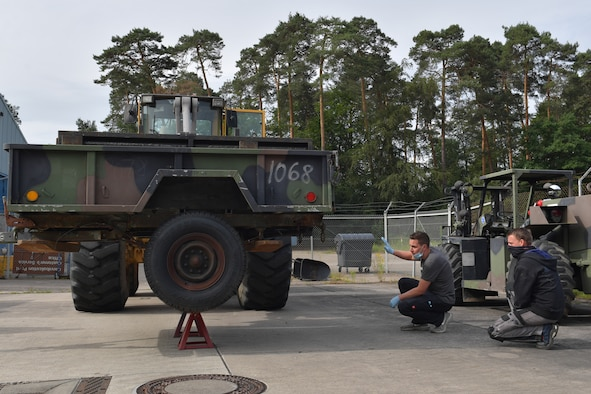 Two mechanics kneeling next to a trailer on a forklift.
