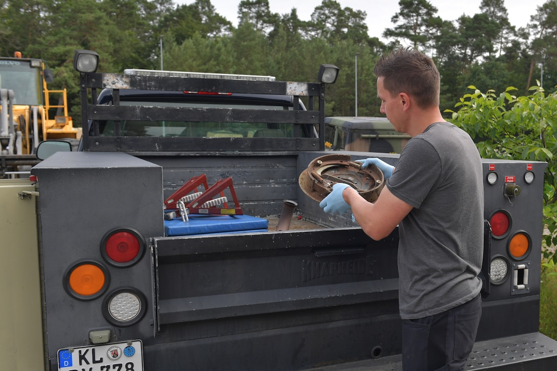 A man placing a brake assembly in a truck bed.