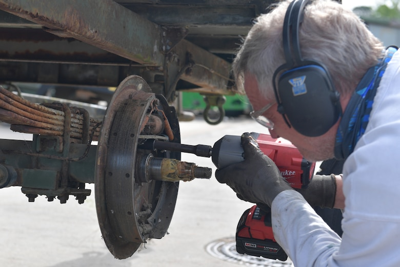 A mechanic working on a brake assembly with a power drill.