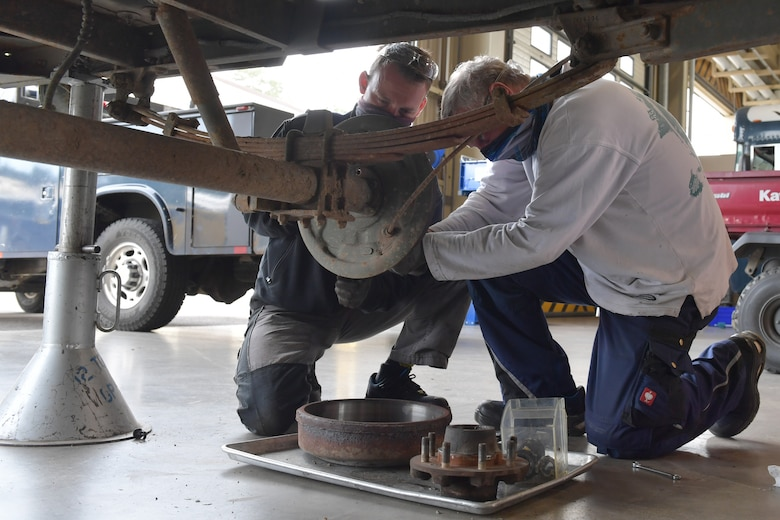 Two mechanics working on a brake assembly.