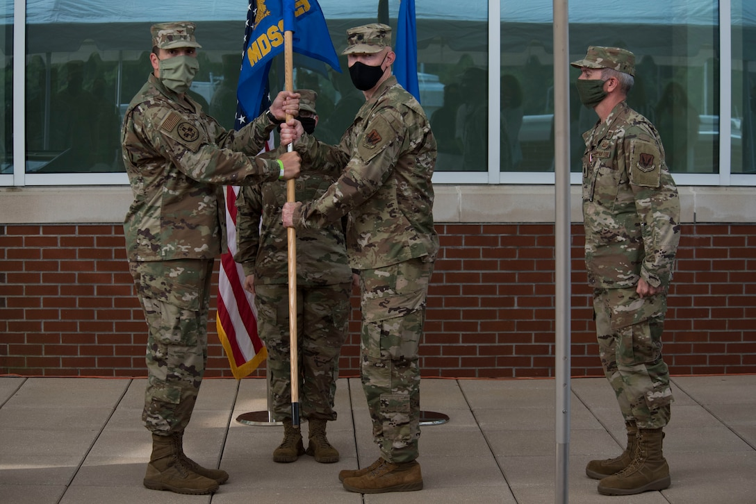 Col. William Malloy, 4th Medical Group commander, passes the guideon to Lt. Col. Joseph Popham, as Popham assumes command of the 4th Medical Support Squadron during a ceremony at the Thomas Koritz Clinic, Seymour Johnson Air Force Base, North Carolina, June 23, 2020. Popham arrived from Joint Base San Antonio Lackland, Texas. (U.S. Air Force photo by Senior Airman Kenneth Boyton)