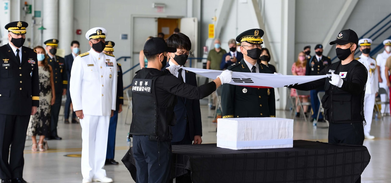 South Korean service members hold a South Korea flag over a box as U.S. military leaders stand at attention nearby.