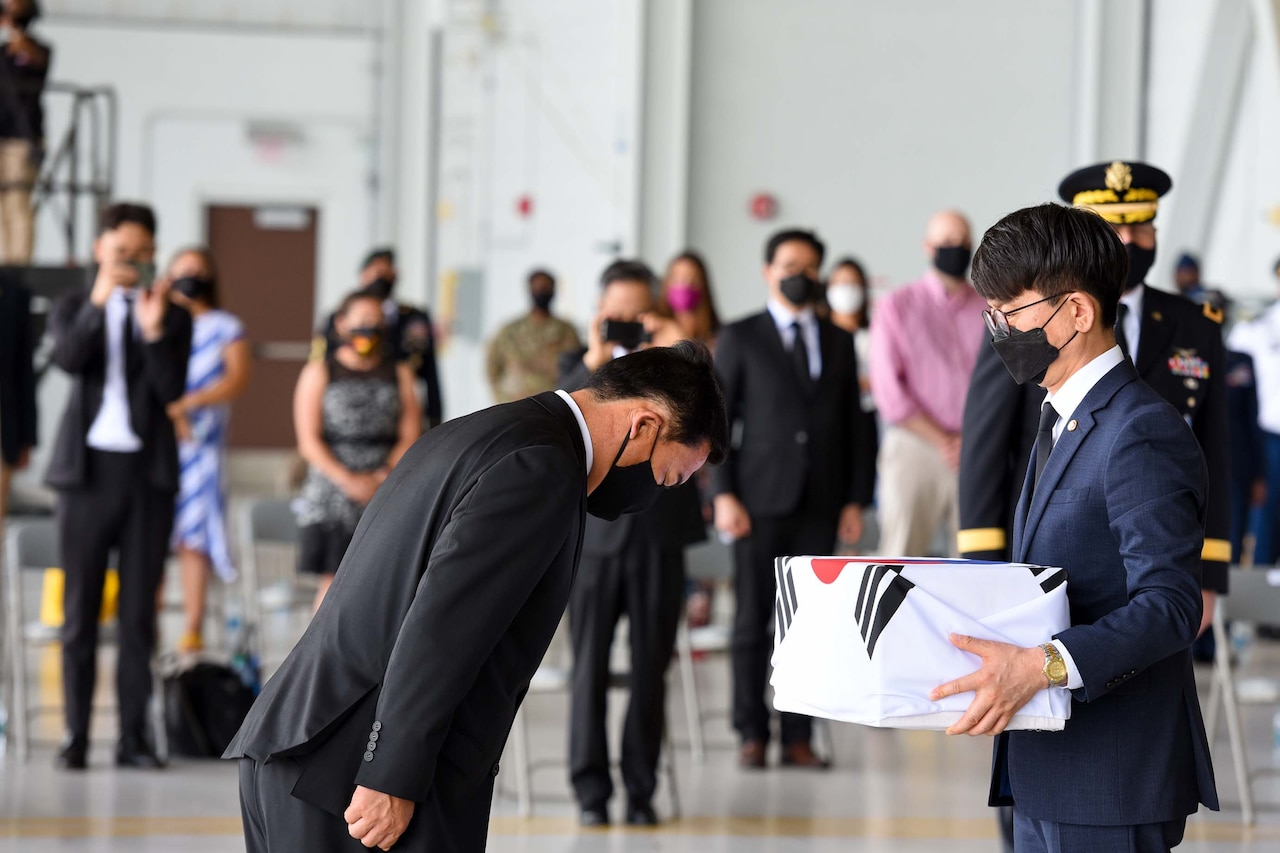 A South Korean official bows at the waist as another official holds a box wrapped in a South Korea flag.