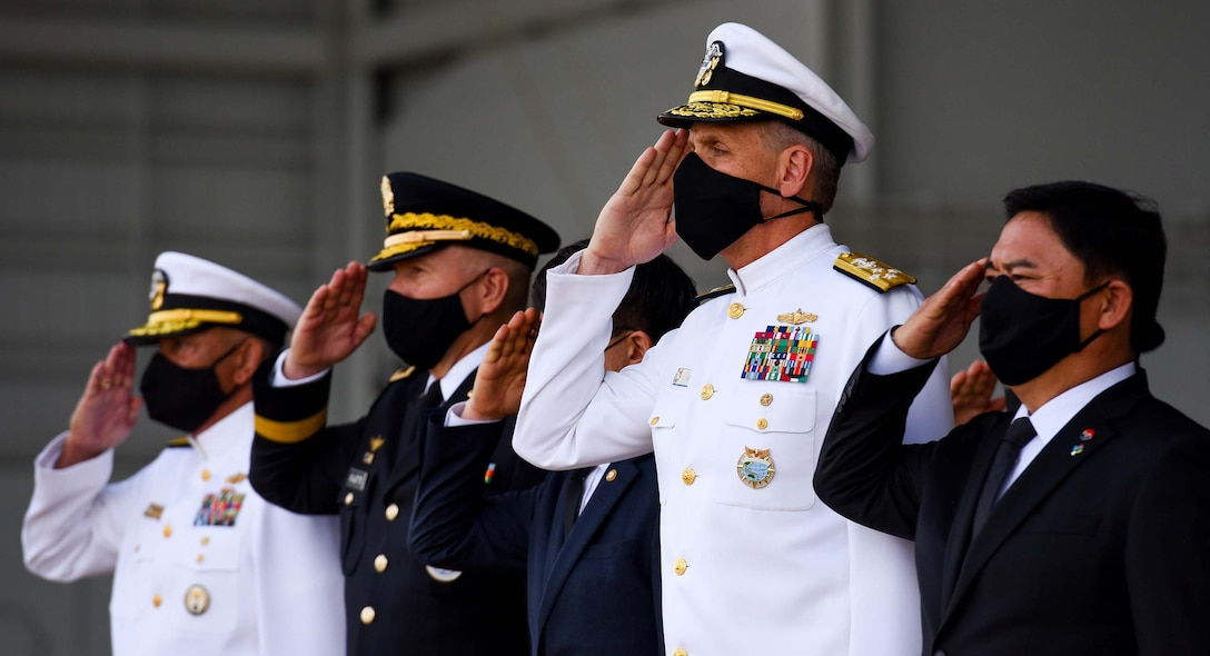 U.S. military and South Korean civilian leaders wearing face masks hold a solemn salute.