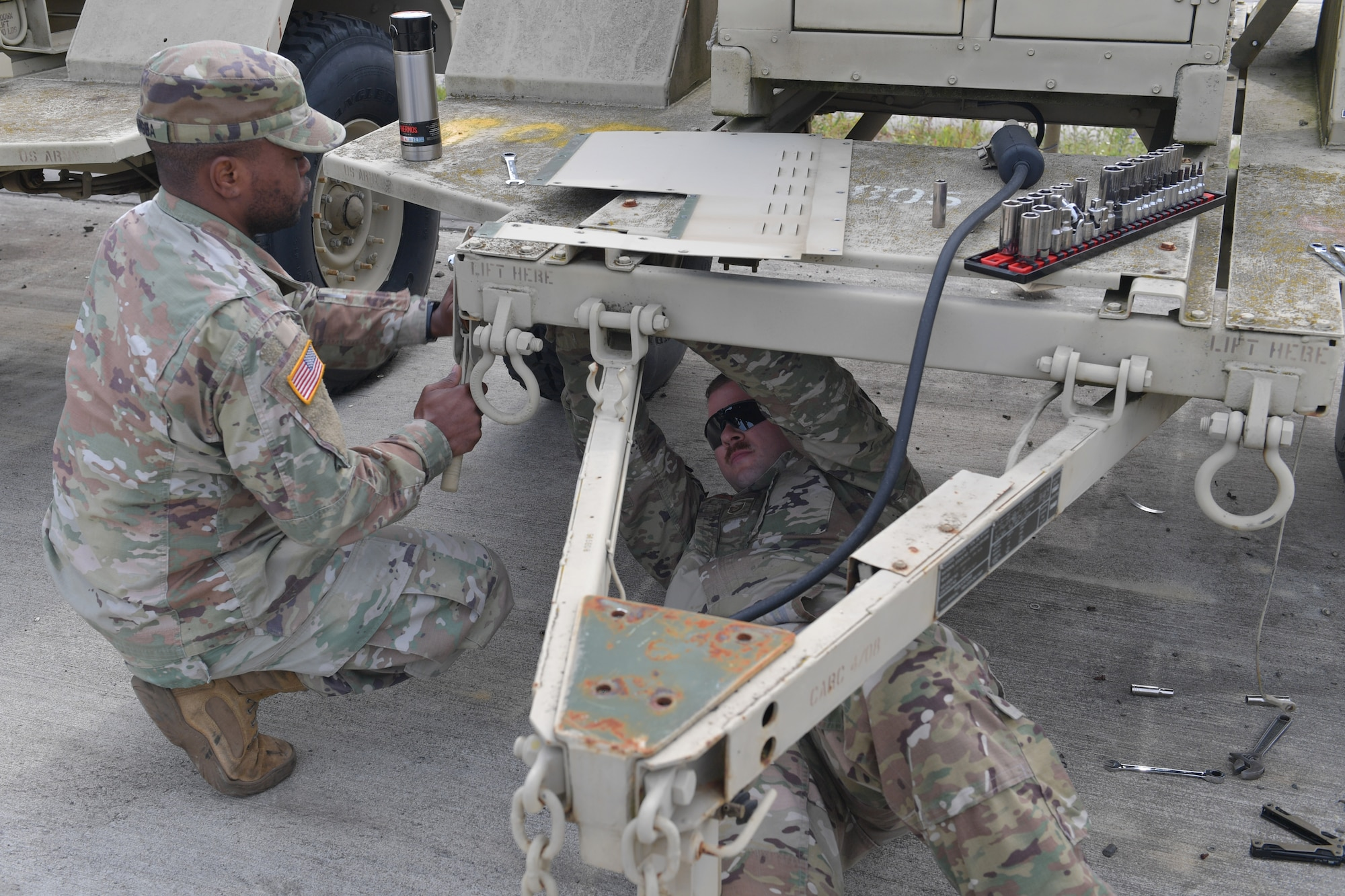 Two men working on a trailer.