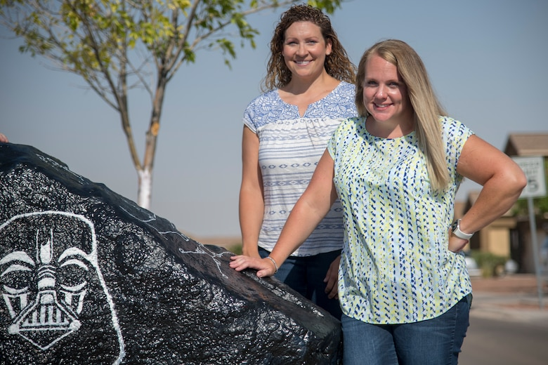 "Maj. Naomi Donovan, left, 924th Aircraft Maintenance Squadron commander and 2018 49th Mission Support Group key spouse, and Jackie Ottesen, 6th Attack Squadron key spouse, pose for a photo at the ""Holloman rock,"" June 23, 2020, on Holloman Air Force Base, N.M. Holloman key spouses paint this decorative rock approximately every two weeks to highlight fun events, holidays and general base awareness activities in order to promote community, cohesion and aid in putting a smile on Team Holloman members' faces. (U.S. Air Force photo by Senior Airman Collette Brooks)"